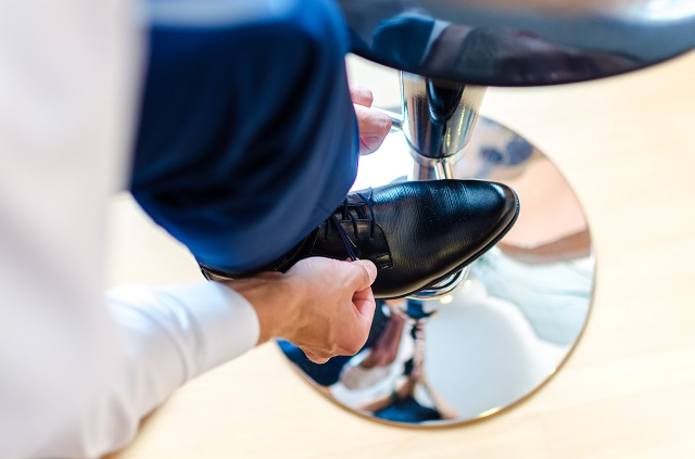 Business man is putting on elegant shoes
