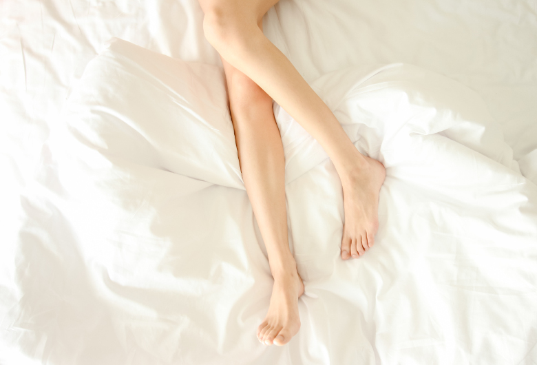 Beautiful female legs not covered top view void. Woman sticked her legs in white bed. Naked legs with white pedicure on end of bed. Some free space