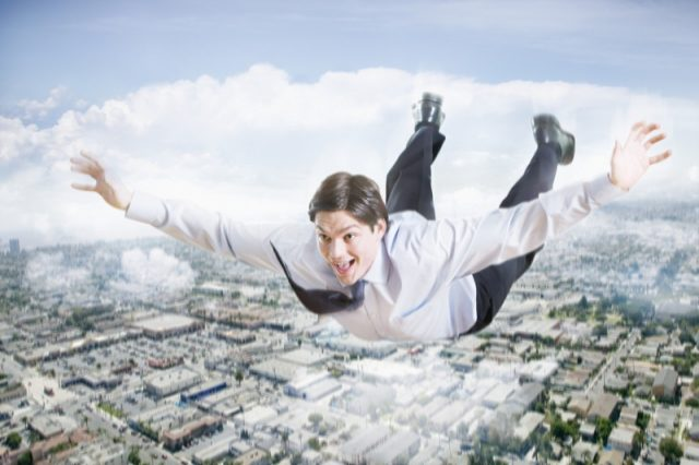 Excited Businessman Flying In The Clouds