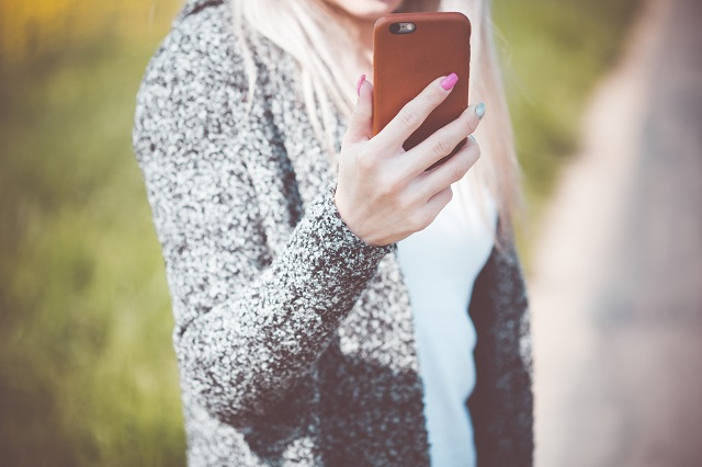 young-woman-holding-her-iphone-in-leather-case-picjumbo-com (1)