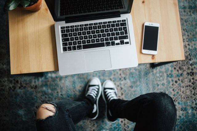 kaboompics_Woman in ripped jeans and black sneakers with a silver laptop on a wooden table