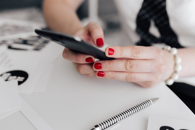 kaboompics_Businesswoman uses her mobile phone at her desk (1)