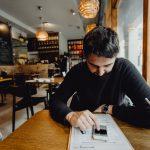 kaboompics_Man using his mobile phone in the restaurant (1)