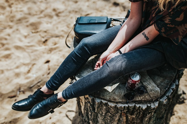 kaboompics_Beautiful blonde woman relaxing with a can of coke on a tree stump by the beach (1)
