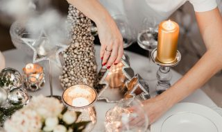 kaboompics_A woman decorates a Christmas table with silver decorations and white porcelain tableware