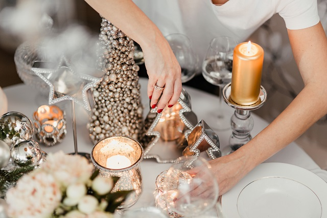 kaboompics_A woman decorates a Christmas table with silver decorations and white porcelain tableware (1)