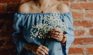 kaboompics_A woman in a blue dress holds a branch of Baby's Breath flower (1)