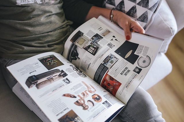 kaboompics_Woman reading a designer magazine on a couch
