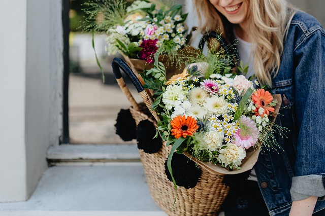 kaboompics_Young woman with basket full of flowers (3)