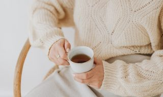 kaboompics_A woman in a warm sweater drinks tea