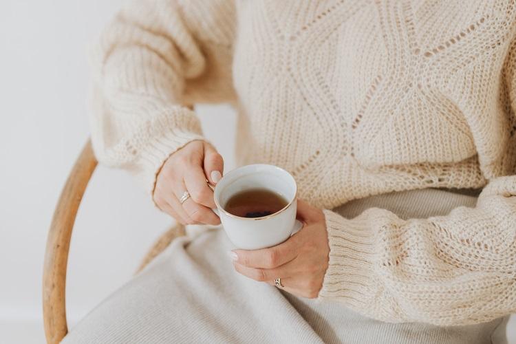 kaboompics_A woman in a warm sweater drinks tea