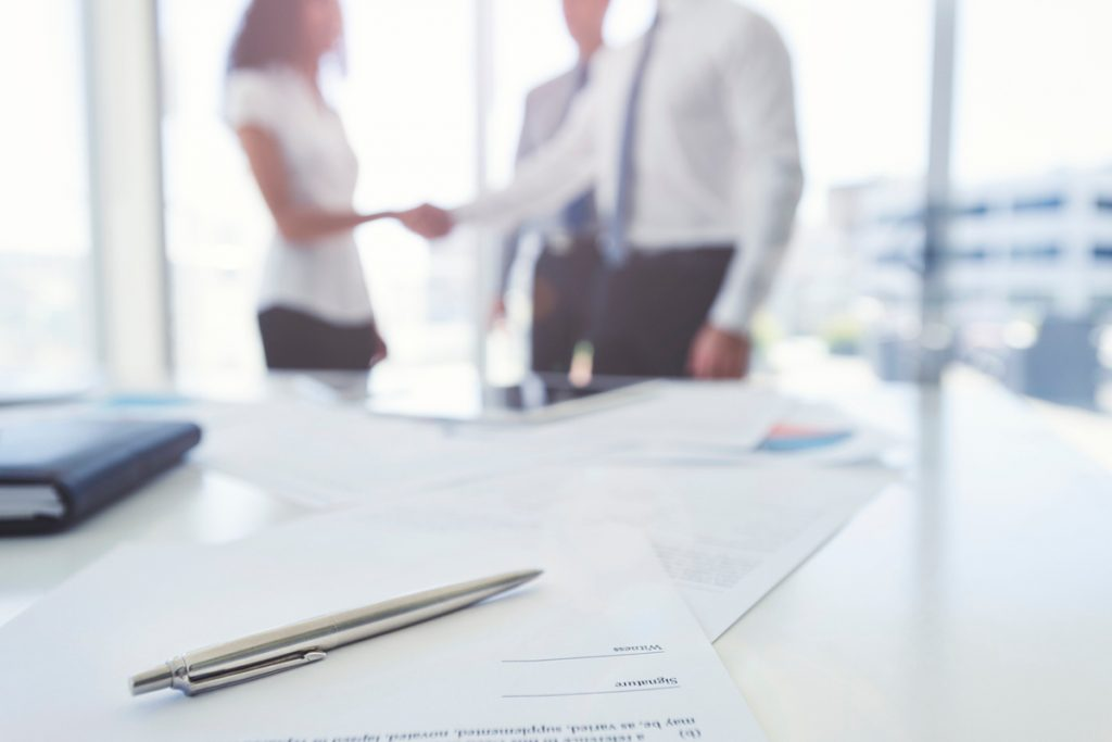 Business-woman-and-business-man-shaking-hands-with-a-contract.-1020863514_1258x837