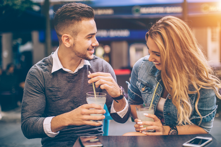 Young couple sitting at restaurant and drinking lemonade. They are happy an joyful. Having such a nice day.