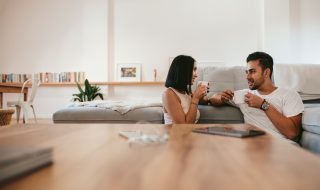Young couple relaxing by the couch with cup of coffee in the living room. Man and woman sitting together at home having coffee and talking.