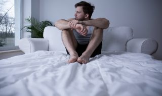 Man sitting on his bed