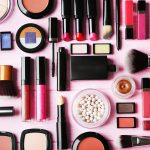 Flat lay of makeup cosmetics on pink background
