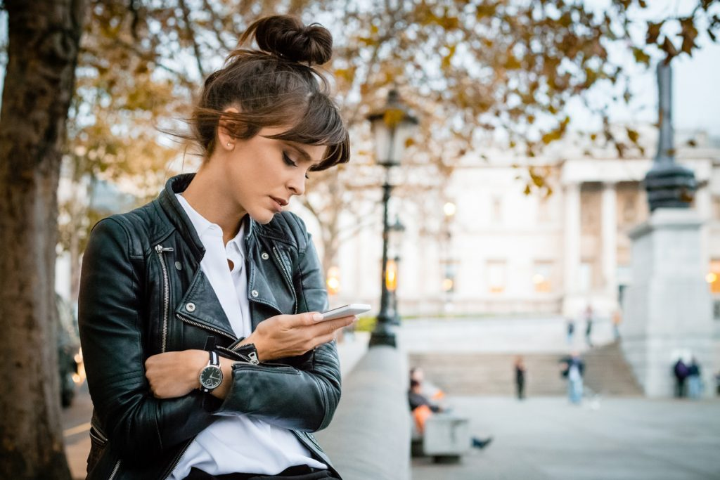 Worried woman using smart phone at Trafalgar Square in London, autumn season