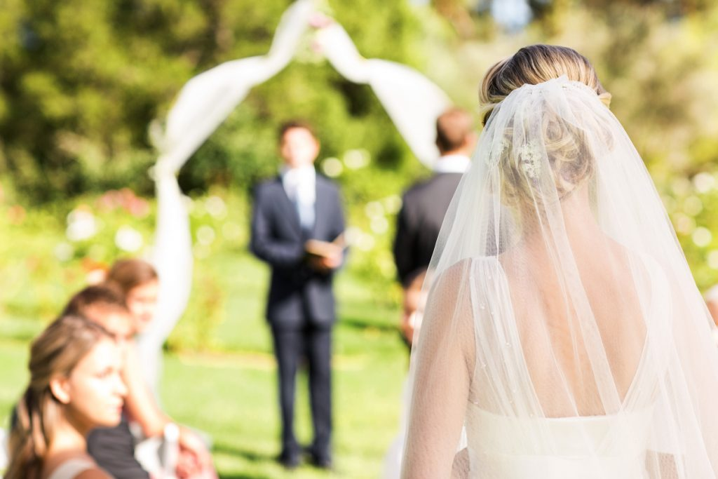 Bride Wearing Veil Walking Down The Aisle During Garden Wedding