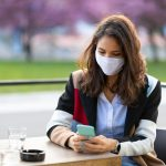 Woman with protective face mask using phone at the cafe table