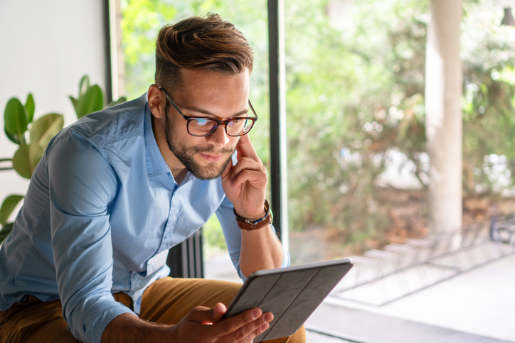 Young amiling Man looking at digital tablet