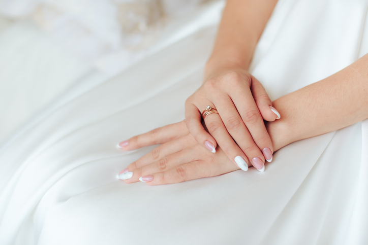 hands of the bride in a white dress with a beautiful manicure 1
