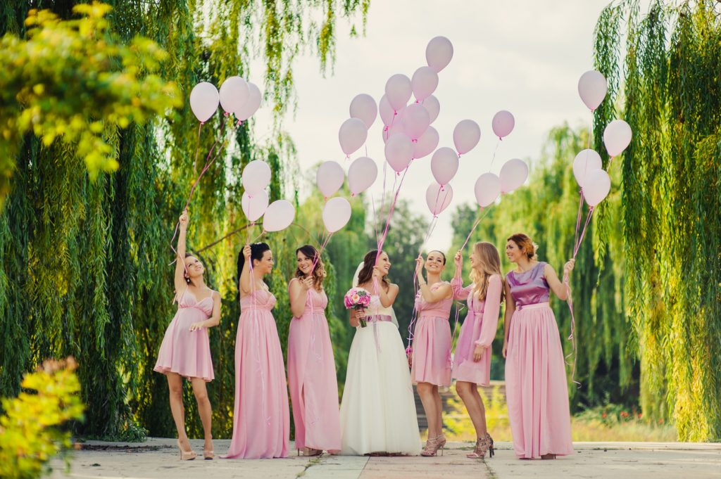 Bride with bridesmaids in pink dresses for a walk