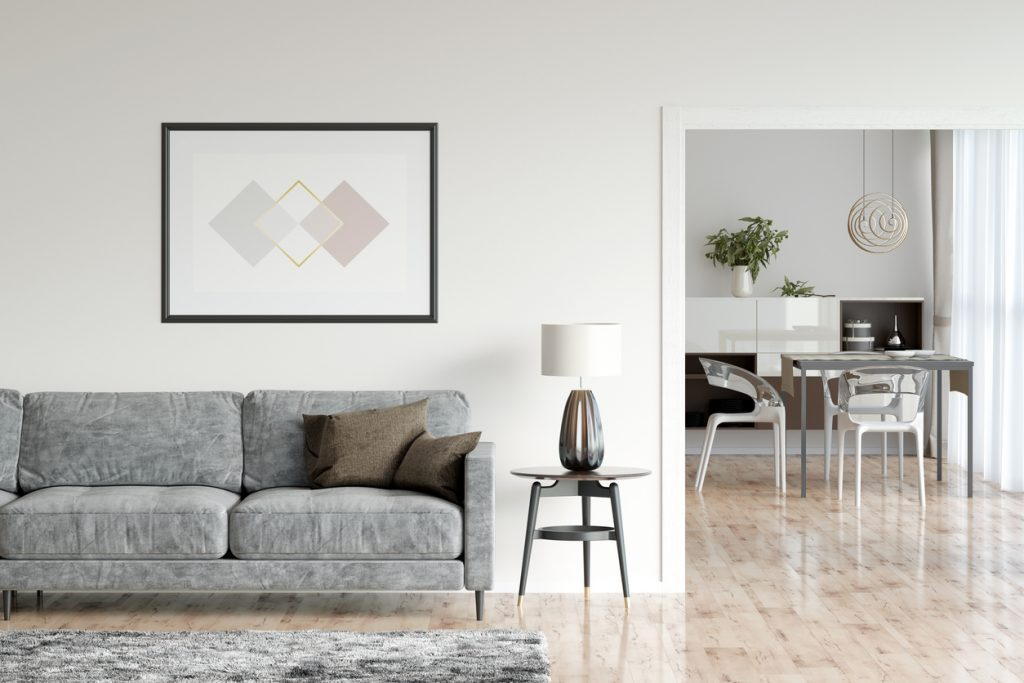 Bright living room interior with parquet floor, shaggy carpet, horizontal poster, the reading lamp next to a cozy gray sofa, overlooking the dining room. Front view.