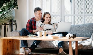 Family life. Couple at home with laptop