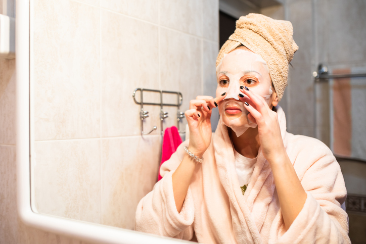 A beautiful woman pressing a sheet mask onto her face