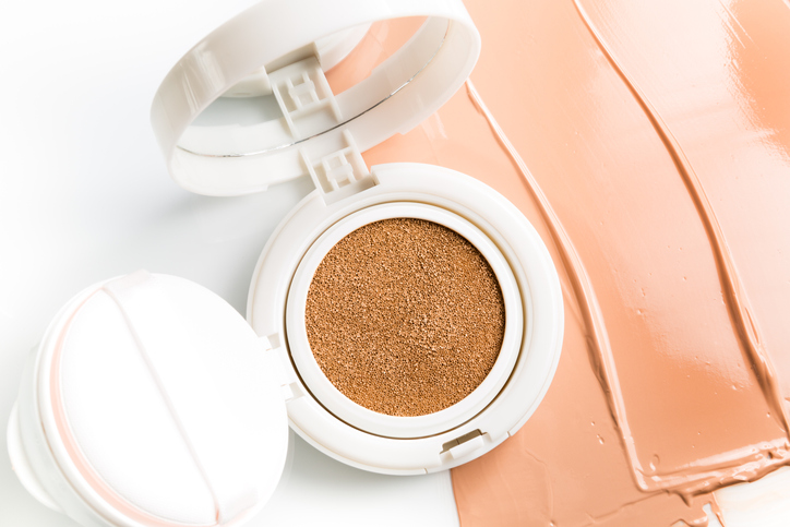 Foundation cushion with sponge and puff on white background.