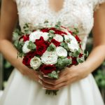 The girl in a wedding dress with her back holds a bouquet of flowers in her hand , wedding photo, body