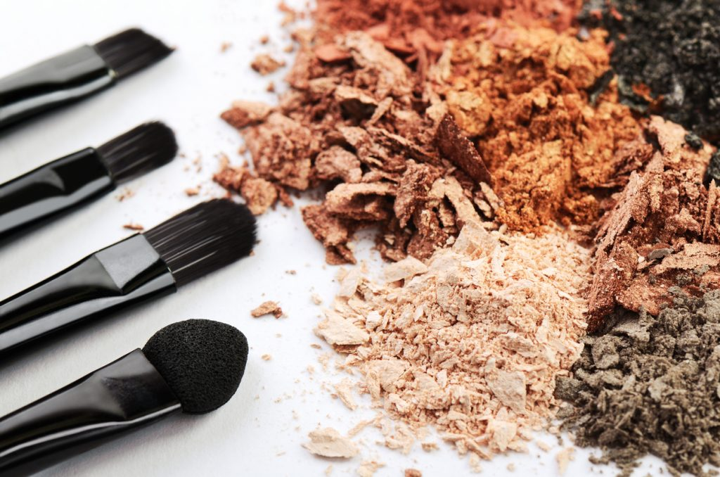 four makeup brushes and crumbled eyeshadows of different colors