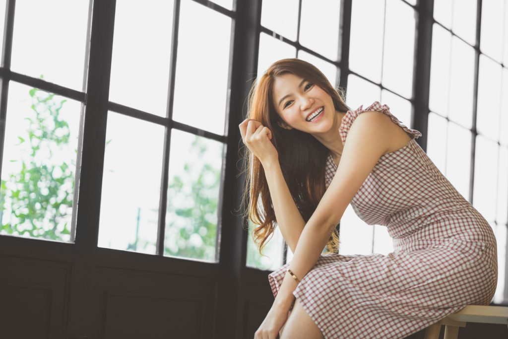 Portrait of cute and beautiful Asian girl smiling in coffee shop or modern office with copy space. Happy people, modern lifestyle, or women fashion advertisement concept